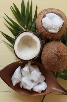 Kokosnussöl. große stücke kokosöl in einer kokosnussschale, kokosnussnüsse auf gelbem holzbrett. bio bio kokosöl