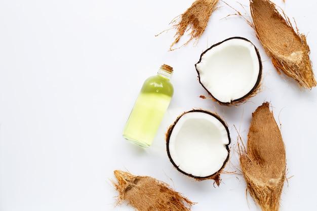 Kokosnussöl mit kokosnüssen auf weiß