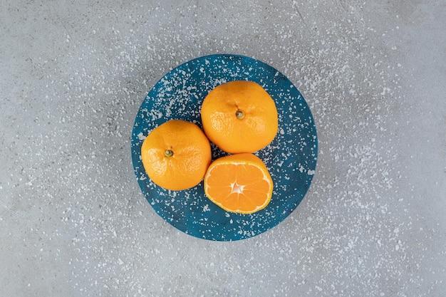 Kokosnusspulver über orangenplatte auf marmorhintergrund gestreut.