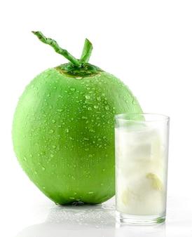 Kokosnusssaft und das trinken des süßen kokosnusswassers im glas lokalisiert auf weiß