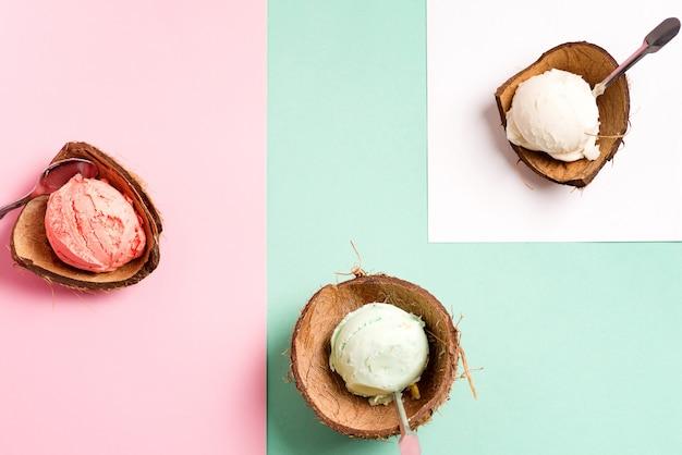 Kokosnussschalen mit frischem natürlichem buntem eis auf einem duotone mit papierblatt