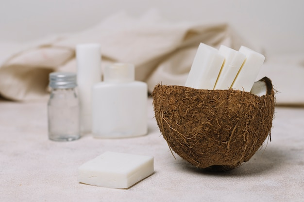 Kokosnussseifenstücke in der kokosnussschüssel mit ölen
