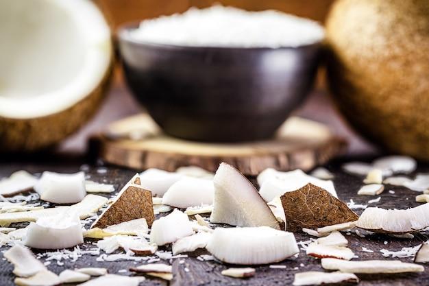 Kokosnussstücke, -schale und -chips auf einem rustikalen holztisch, kulinarische zutat, mit reifer kokosnuss im hintergrund