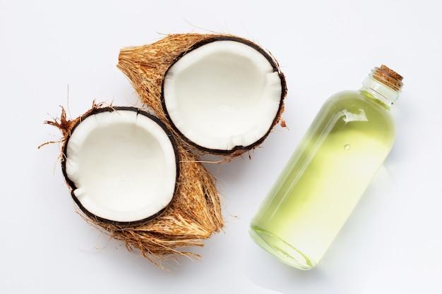 Kokosöl mit kokosnüssen auf weißem hintergrund.