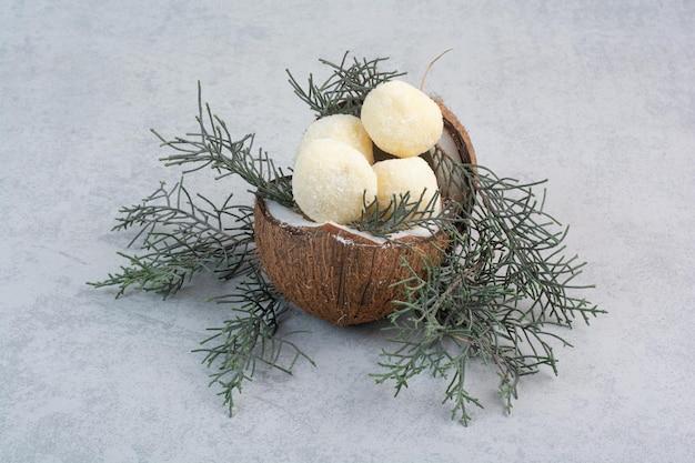 Kokosplätzchen innerhalb der kokosnuss auf grauem hintergrund. foto in hoher qualität