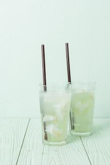 Kokoswasser oder kokossaft im glas mit eiswürfel