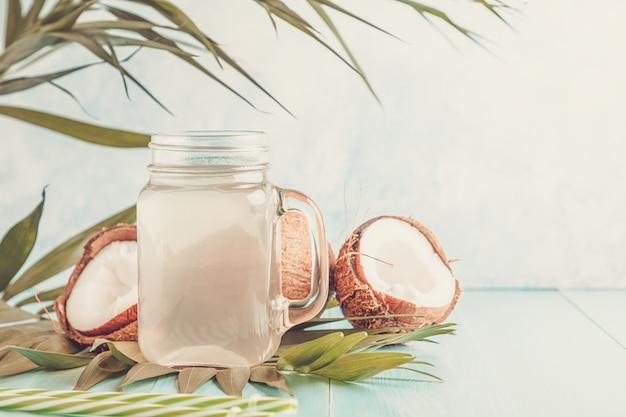 Kokoswasser und kokosnüsse auf einem hellen pastell