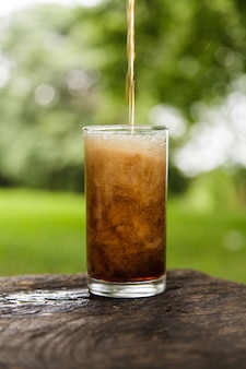 Kolabaum, der in ein glas gießt