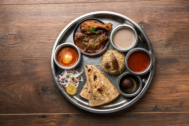 Kolhapuri chicken thali ist eine beliebte indische, asiatische speisenplatte bestehend aus geflügelfleisch, eiercurry mit chapati, reis, salat und süßem gulab jamun