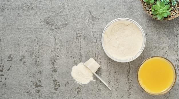Kollagenproteinpulver in einem plastikmesslöffel und glas auf grauem stein, flach liegend.