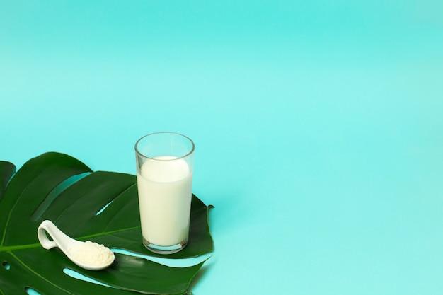 Kollagenpulver im löffel und im glas milch übersteigen auf palmblatthintergrund