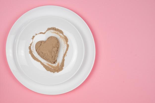 Kollagenpulver oder -protein wird zufällig über die oberfläche der platte verteilt. herzförmiger leerer raum. ergänzung zu einer gesunden ernährung. der 14. februar.