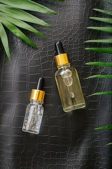 Kollagenserum oder hyaluronserum in tropfer auf schwarzem krokodilhaut-texturhintergrund mit palmblättern. kosmetikflasche für die hautpflege. kosmetik gesundheit gesicht haut schönheit vertikal.