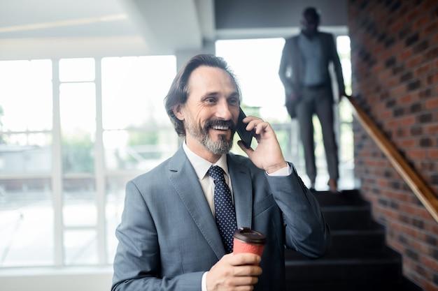 Kollege anrufen. grauhaariger mann, der kaffee zum mitnehmen hält und lächelt, während er kollege anruft