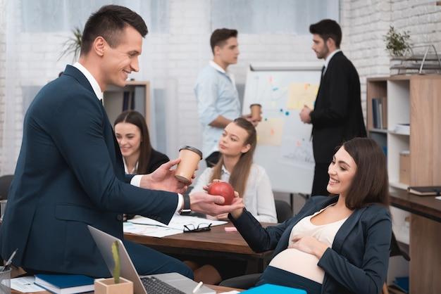 Kollege, der der schwangeren arbeitskraft im büro lebensmittel gibt