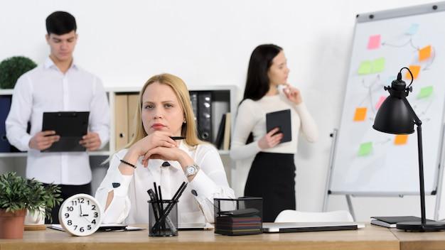 Kollege, der hinter der ernsten jungen geschäftsfrau am arbeitsplatz steht