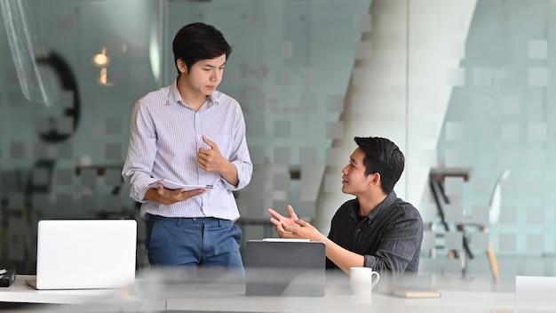 Kollegen bemannen die unterhaltung mit dokumentenschreibarbeit im modernen büro.
