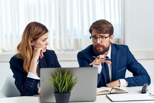 Kollegen chatten im büro vor einer laptop-technologie