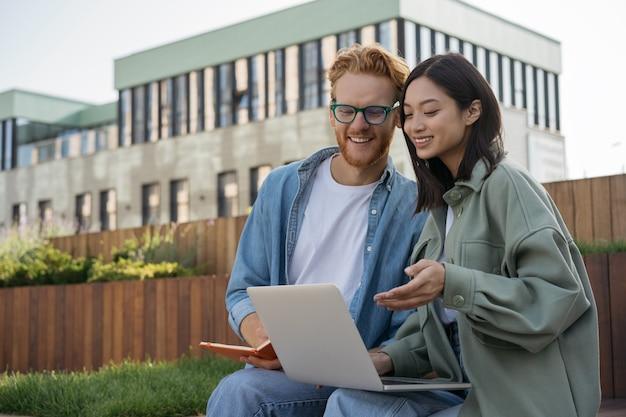 Kollegen, die die kommunikation mit laptops nutzen, arbeiten zusammen