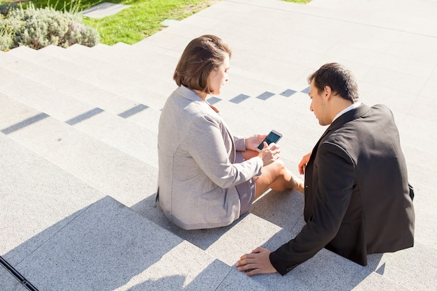 Kollegen, die draußen smartphone auf treppe verwenden