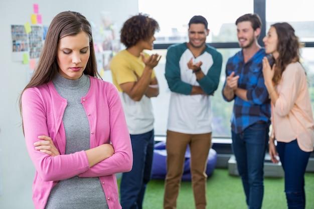 Kollegen, die eine traurige weibliche führungskraft schikanieren