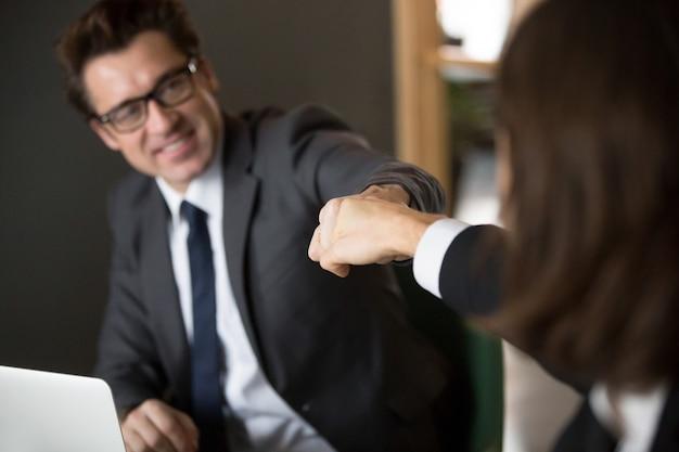 Kollegen, die fäuste geben, stoßen das feiern der geteilten geschäftsleistung