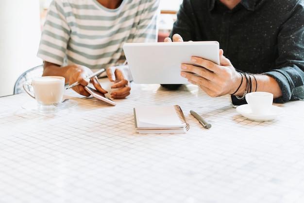 Kollegen, die ihre arbeit auf einer tablette besprechen