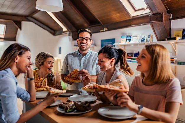 Kollegen, die pizza essen und am mittagessen in coworking büro sprechen.