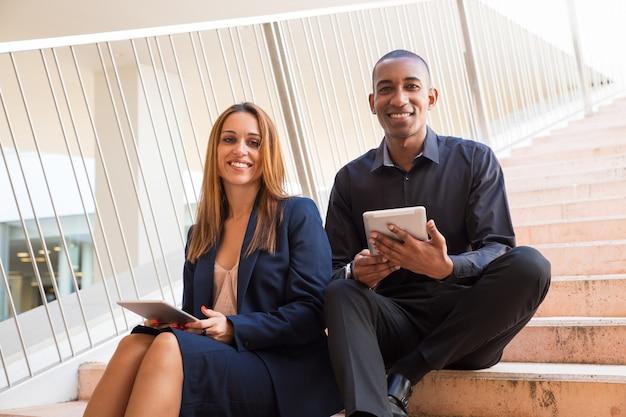 Kollegen, die tablet-computer halten und auf treppe sitzen