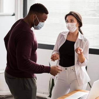 Kollegen, die während einer pandemie mit masken im büro zusammenarbeiten