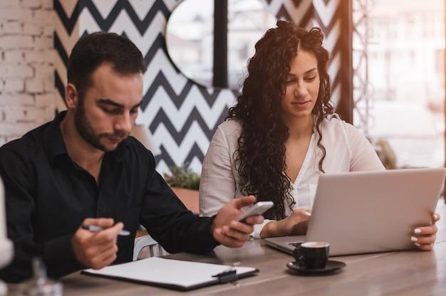 Kollegen, die zusammen an einem computer in einer kaffeestube arbeiten