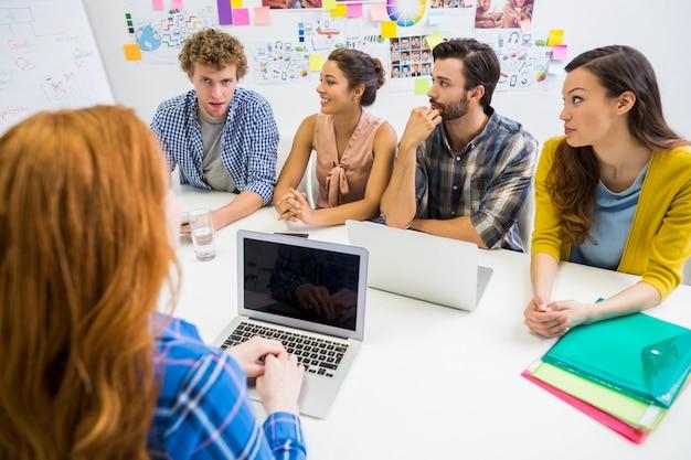 Kollegen diskutieren über laptop mit der führungskraft während des meetings