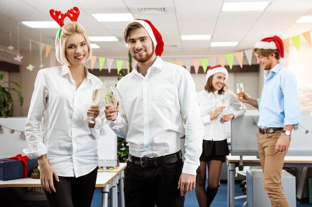 Kollegen feiern weihnachtsfeier im büro und trinken champagner lächelnd.