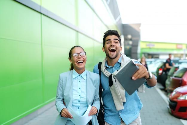 Kollegen gehen auf der straße und lachen, während sie in die kamera schauen.