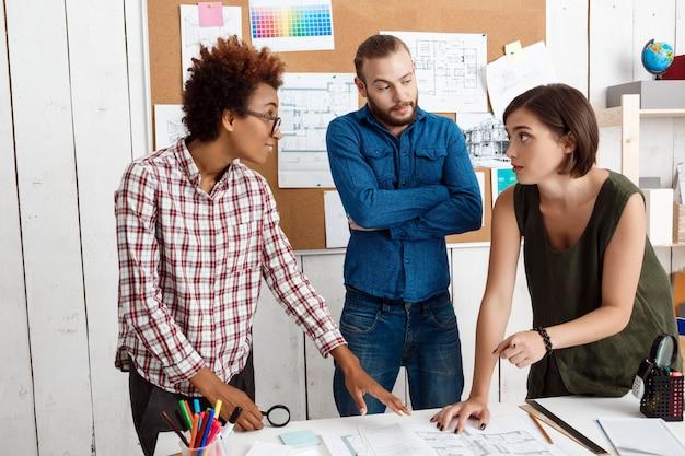Kollegen lächeln, sprechen, zeichnungen diskutieren, neue ideen im büro
