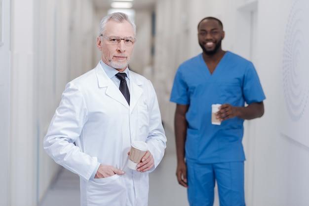 Kollegen mit respekt inspirieren. hübscher erfahrener älterer praktizierender, der in der klinik steht, während er eine tasse kaffee hält und pause mit afroamerikanischem kollegen genießt