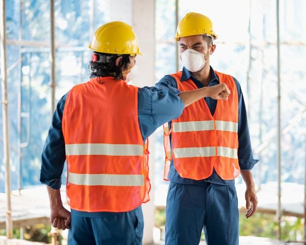 Kollegen mit sicherheitsausrüstung, die mit bauplänen arbeiten