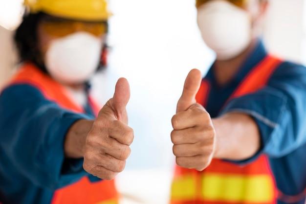 Kollegen mit sicherheitsausrüstung mit ok-zeichen