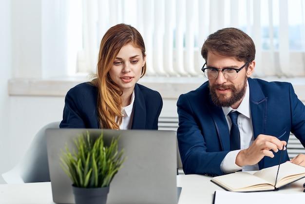 Kollegen sitzen am tisch vor laptop bürotechnik