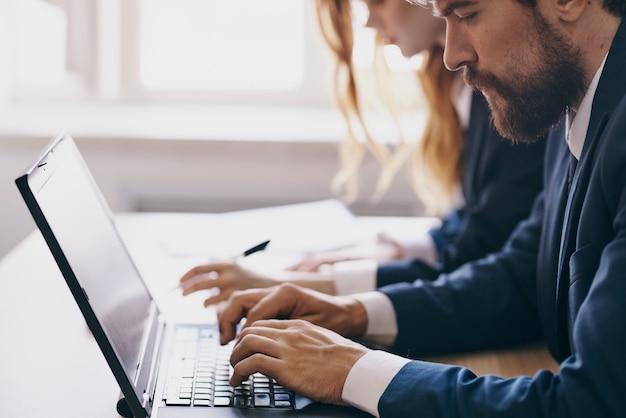 Kollegen sitzen an einem schreibtisch mit einem laptop kommunikations-finanzprofis