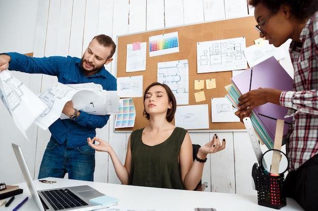 Kollegen streiten, diskutieren zeichnungen, neue ideen, während frau meditiert