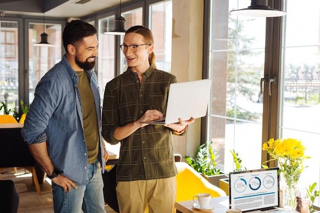 Kollegen und freunde. fröhliche glückliche männer, die zusammenstehen, während sie miteinander sprechen