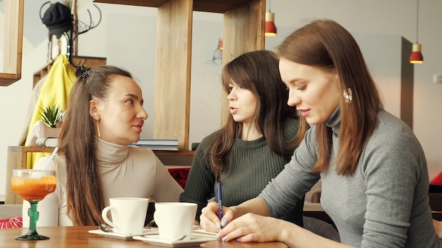 Kollegenfrauen diskutieren gemeinsames projekt im café im coworking center und machen sich notizen in einem notizbuch.