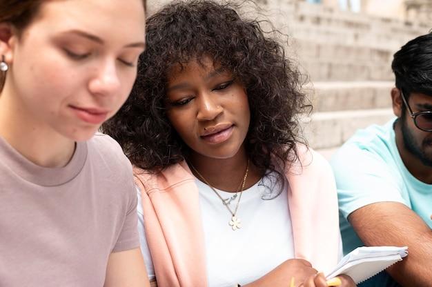 Kolleginnen und kollegen, die vor einer prüfung gemeinsam vor ihrer hochschule lernen