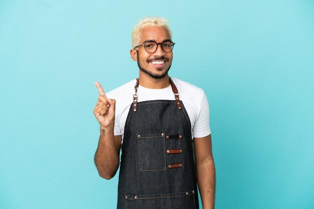Kolumbianischer kellner im restaurant isoliert auf blauem hintergrund, der einen finger im zeichen des besten zeigt und hebt