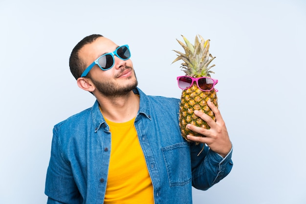 Kolumbianischer mann, der eine ananas mit sonnenbrille hält