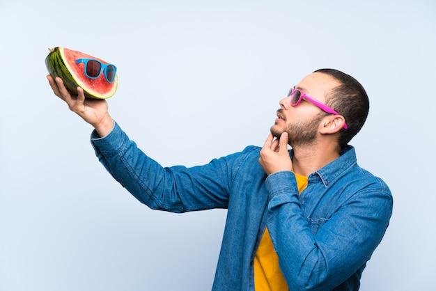 Kolumbianischer mann, der eine wassermelone mit sonnenbrille hält