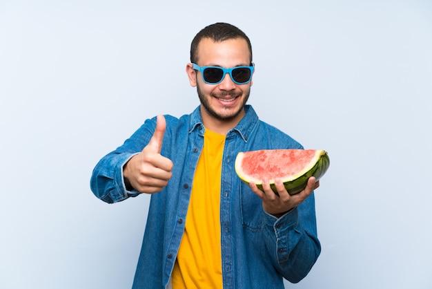 Kolumbianischer mann, der eine wassermelone über blau mit dem daumen hochhält