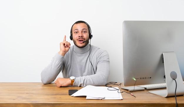 Kolumbianischer mann des telemarketers, der eine idee zeigt den finger oben denkt