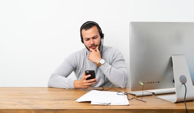Kolumbianischer mann des telemarketers, der eine mitteilung denkt und sendet